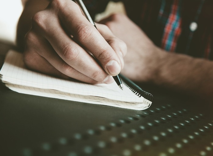 man-writing-in-journal